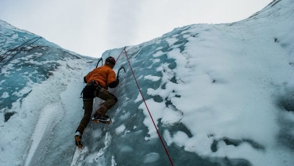 ice climbing a sheer face with a rope