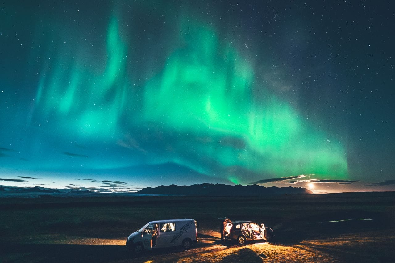 two cars under northern lights