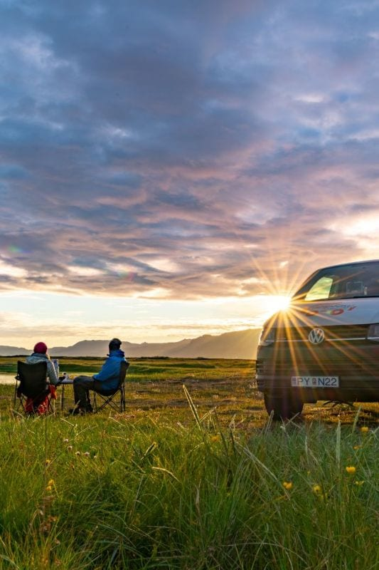 couple sitting by camper at midnight in Iceland
