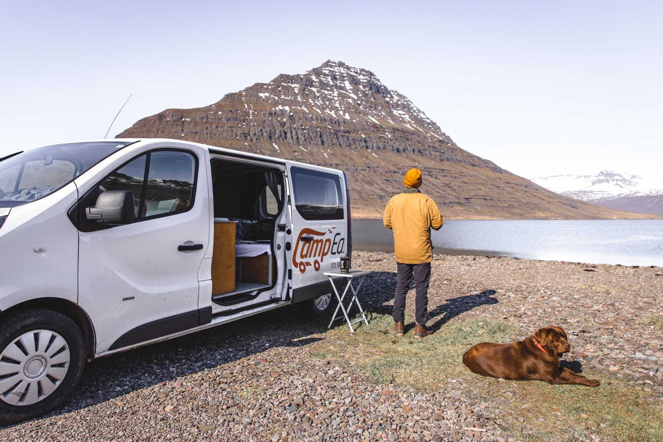 Man and a dog standing next to a camper